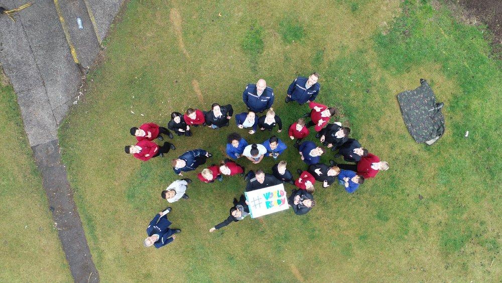Joukko ihmisiä nurmikolla kuvattuna ylhäältäpäin, pitävät kädessään kylttiä missä lukee #WORLDREADY