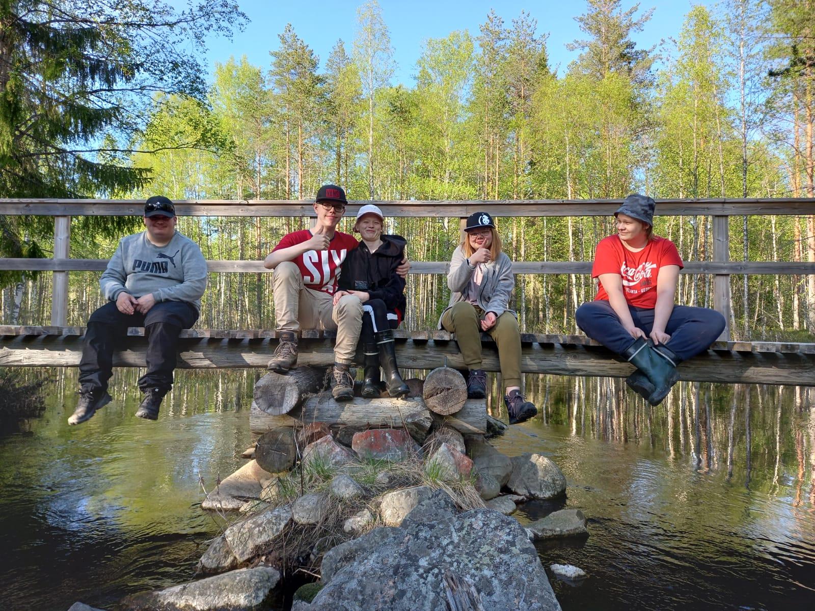 Viisi nuorta istumassa joen ylittävän sillan päällä